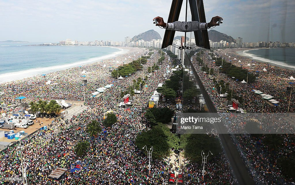 A man reaches out of a hotel window to take a photo as crowds jam Copacabana Beach for Pope Francis' final Mass on his trip to Brazil, with millions expected to attend, on July 28, 2013 in Rio de Janeiro, Brazil. A reported crowd of 3 million faithful jammed the beach for a prayer vigil on the final night of World Youth Day last night. Francis' first international trip as Pope has drawn millions to see the first Pope to hail from Latin America. Brazil has the largest number of Catholics on Earth.