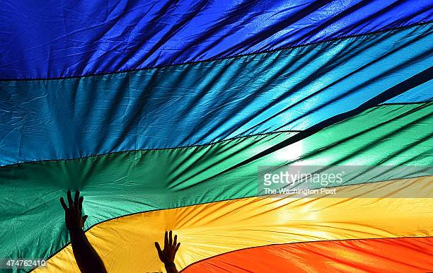 A man reaches out to a large rainbow flag which is placed in support of gay marriage in front of the US Supreme Court in Washington DC April 28 2015