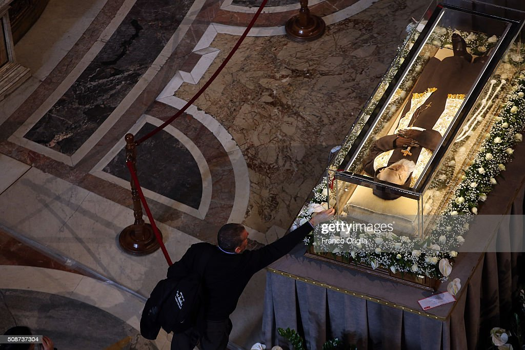 A man reaches towards the corpse and relics of Padre Pio on display in St. Peter's Basilica for veneration by the faithful in connection with the ongoing Extraordinary Jubilee Year of Mercy on February 6, 2016 in Vatican City, Vatican. St. Pius of Pietralcina or San Padre Pio, as he is popularly known around the world was a Capuchin friar with a worldwide reputation during his earthly life as a mystic and miracle-worker, who was also a tireless confessor and laborer in favor of the poor, the sick, and the downtrodden.