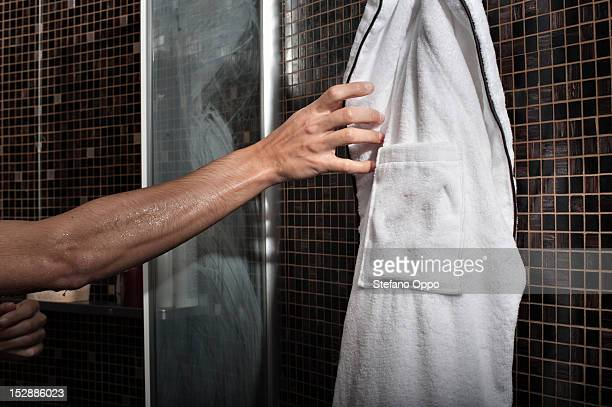 Man reaching for bathrobe in shower