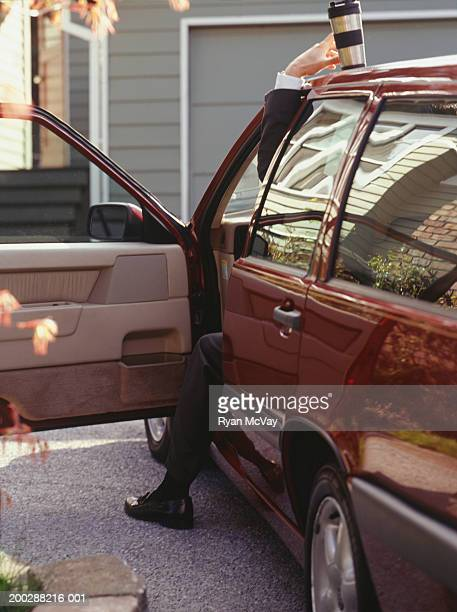 Man reaching for coffee flask on car roof