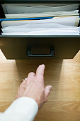 Man reaching for file drawer handle, close-up, overhead view