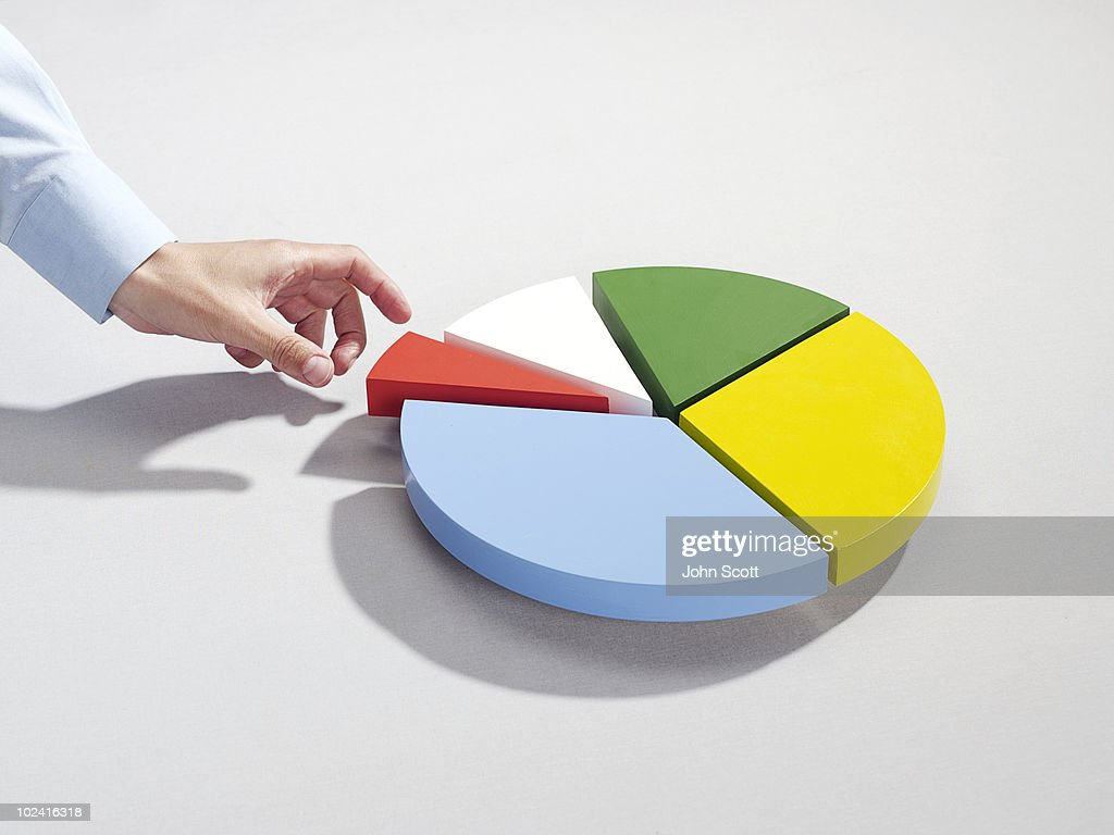 Man reaching for segment of pie chart : Stock Photo