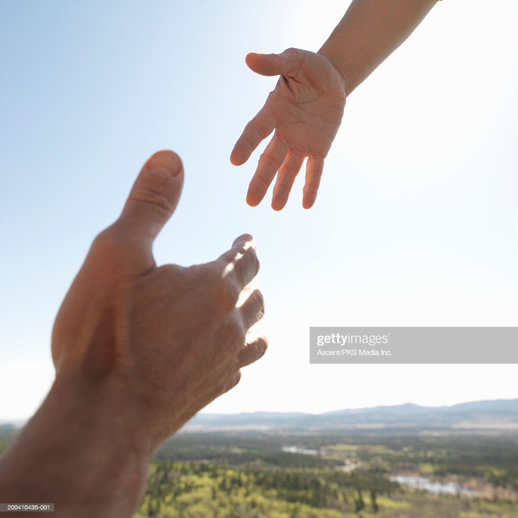 Man reaching for woman's hand, close-up : Stock Photo