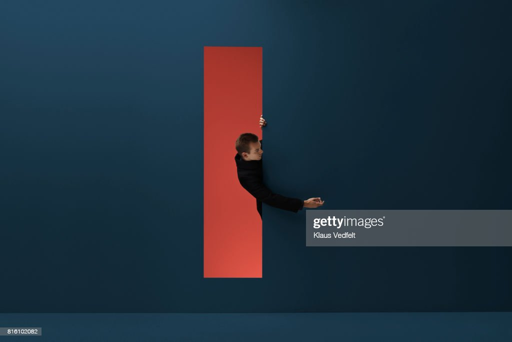 Man reaching hand out threw rectangular opening in coloured wall : Stock Photo