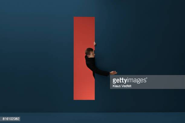 Man reaching hand out threw rectangular opening in coloured wall