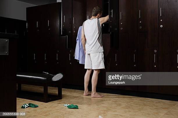 Man reaching into locker in locker room, rear view