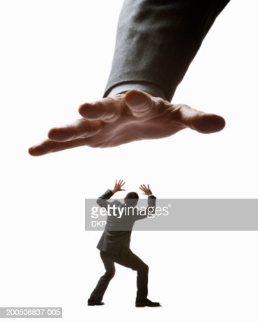 Man reaching out to grab young businessman (Digital Composite) : Stock Photo
