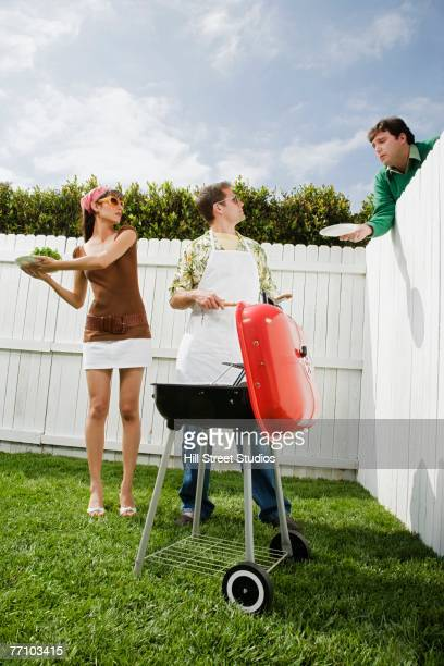 Man reaching plate over fence at barbecue