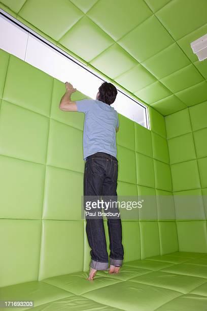 Homme avoir à regarder par la fenêtre en Pièce capitonnée