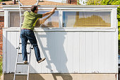 White, middle aged male paints white trim of old urban home, and almost falls from ladder