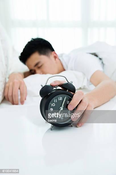 Man reaching to turning off alarm clock