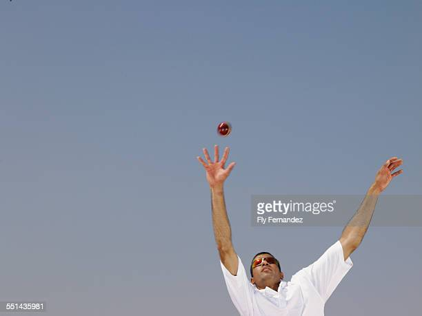 Man Reaching Up to Catch Ball