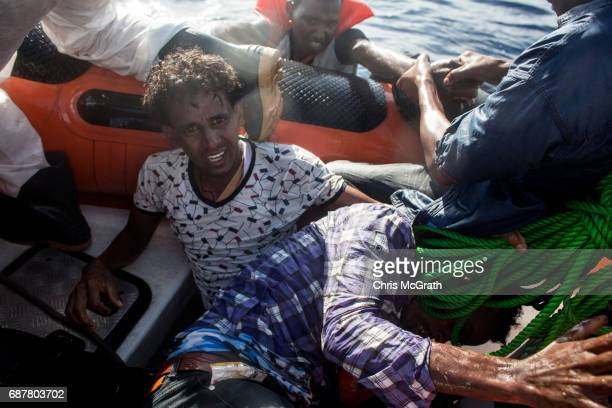 A man reacts after being pulled into a rescue boat from the Migrant Offshore Aid Station 'Phoenix' vessel on May 24 2017 off Lampedusa Italy The...