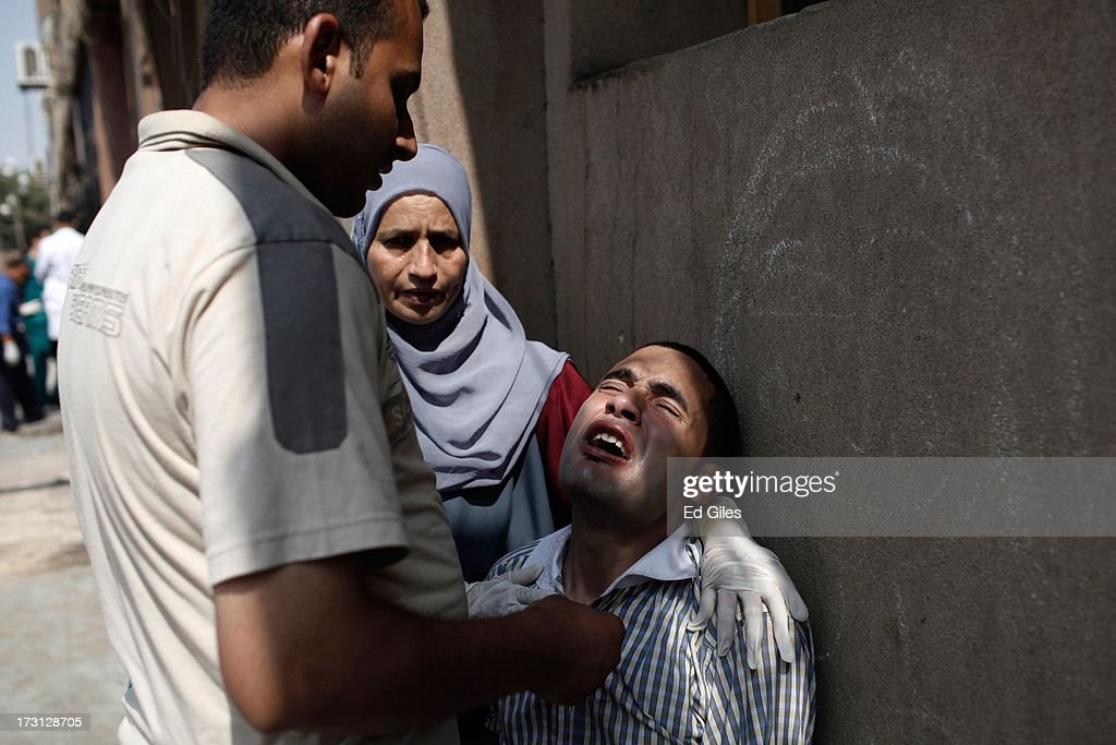 A man reacts after seeing the body of a family member, allegedly killed during a shooting at the site of a pro-Morsi sit-in in front of the headquarters of the Egyptian Republican Guard, at the Liltaqmeen al-Sahy Hospital in Cairo's Nasr City district on July 8, 2013 in Cairo, Egypt. Egyptian health ministry officials are reporting at least 42 people were killed and more than 300 injured in the incident early on Monday morning, which allegedly occurred as supporters of deposed Egyptian President Mohammed Morsi attending the sit in were performing dawn prayer. The demonstrators were demanding the release of Morsi, who they believe is being held inside the Republican Guard headquarters.