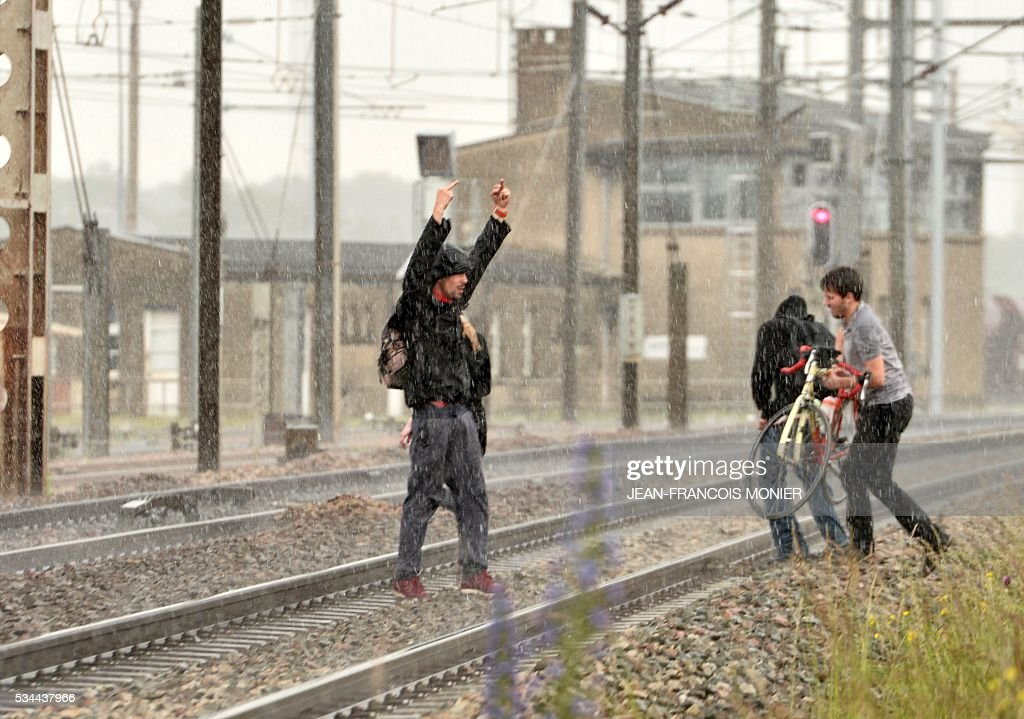 A man reacts as he crosses railway lines during a protest against the government's labour law reforms in Rennes, on May 26, 2016. The French government's labour market proposals, which are designed to make it easier for companies to hire and fire, have sparked a series of nationwide protests and strikes over the past three months. Masked youths clashed with police and striking workers blockaded refineries and nuclear power stations on May 26 as an escalating wave of industrial action against labour reforms rocked France. / AFP / JEAN