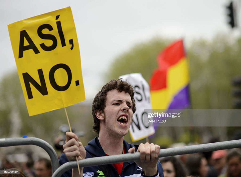 A man reacts as he holds a placard reading 'Not like this' in front of fences blocking the street leading to the Spain's parliament (Las Cortes) during an anti-government demonstration in Madrid on April 25, 2013. A thousand of people, mostly youths, gathered today evening near the Spanish parliament in Madrid in response to a call by a hardline protest movement for demonstrators to 'Besiege Congress' indefinitely to force the government to quit.