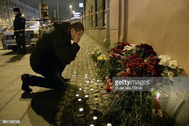TOPSHOT A man reacts as he places flowers in memory of victims of the blast in the Saint Petersburg metro outside Technological Institute station on...