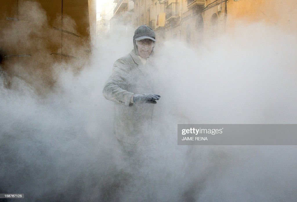 A man reacts as he takes part in the battle of 'Enfarinats', a floor fight in the town of Ibi, in the south-eastern Spain on December 28, 2012. For 200 years Ibi's citizens annually celebrate with a battle using flour, eggs and firecrackers outside the city townhall. AFP PHOTO/ JAIME REINA