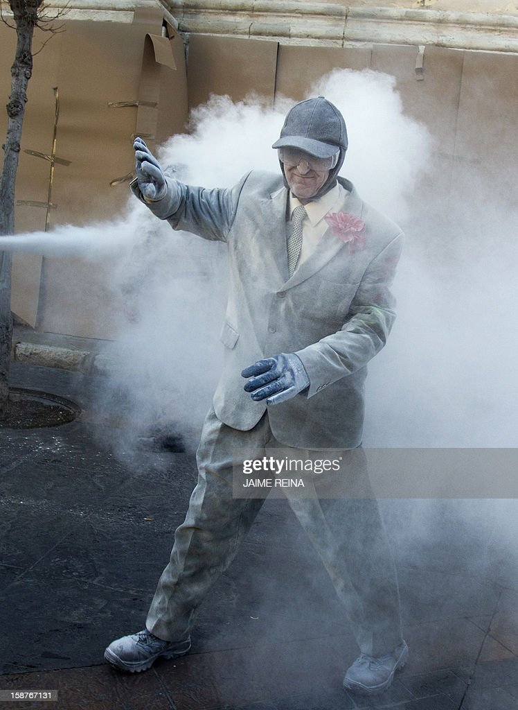 A man reacts as he takes part in the battle of 'Enfarinats', a floor fight in the town of Ibi, in the south-eastern Spain on December 28, 2012. For 200 years Ibi's citizens annually celebrate with a battle using flour, eggs and firecrackers outside the city townhall.