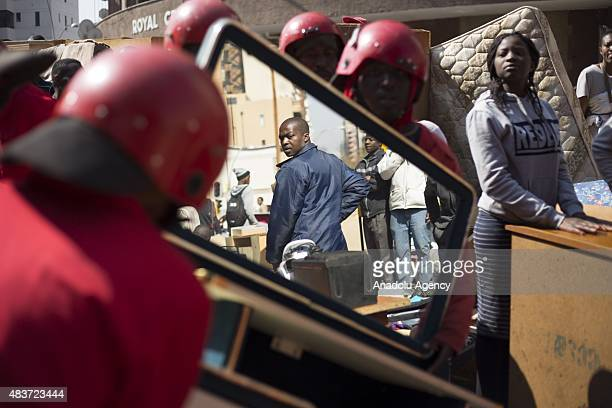 A man reacts as members of the so called 'Red Ants' private security company carry household items belonging to residents of the Williston Building...