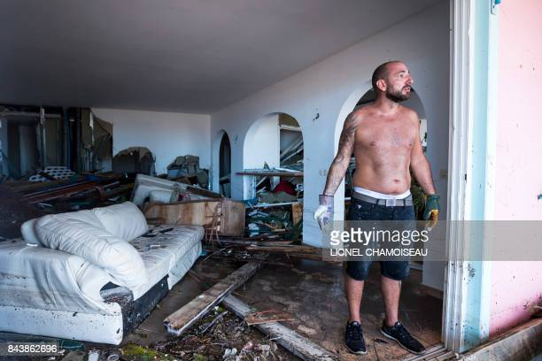 A man reacts as stands in his destroyed home on September 7 2017 in Orient Bay on the French Carribean island of SaintMartin after the passage of...