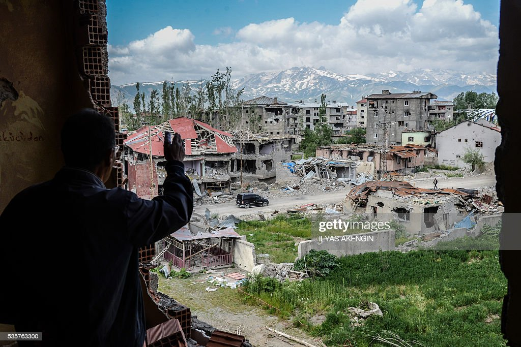 A man reacts from his balcony as he sees damaged buildings after heavy fightings between Turkish government troops and Kurdish fighters during the curfew in the southeastern Turkey Kurdish town of Yuksekova, near the border with Iraq and Iran, on May 30, 2016. / AFP / ILYAS