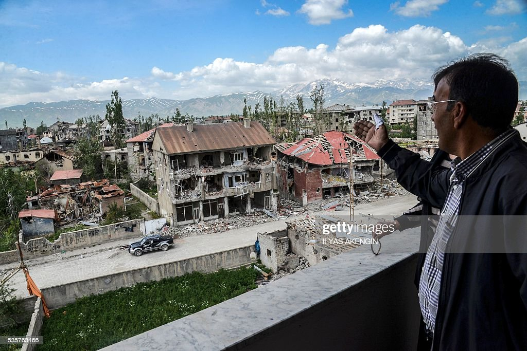 A man reacts from his balcony as he sees damaged buildings after heavy fightings between Turkish government troops and Kurdish fighters after the curfew in the southeastern Turkey Kurdish town of Yuksekova, near the border with Iraq and Iran, on May 30, 2016. / AFP / ILYAS