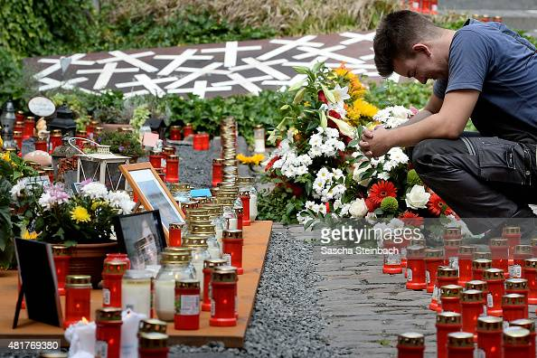 A man reacts looking at candles and flowers left by mourners at the makeshift memorial to victims of the Love Parade disaster on its fifth...