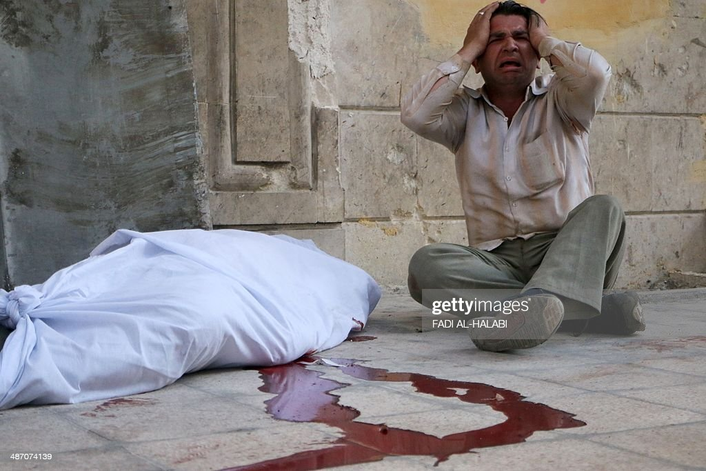A man reacts next to a body wrapped in shrouds following a reported bombardment with explosive-packed 'barrel bombs' by Syrian government forces in the Al-Mowasalat neighborhood in the northern Syrian city of Aleppo on April 27, 2014. Aleppo is divided between government and opposition control, and clashes on the ground, rebel fire and regime aerial bombardment have all increased there in recent weeks.