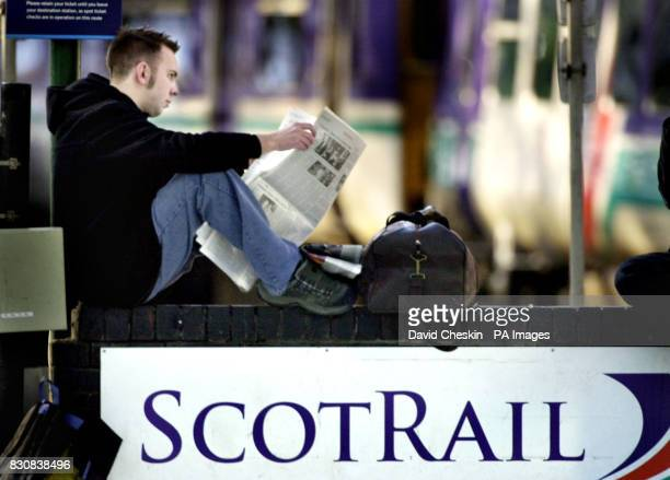 A man read the paper as he waits at Edinburgh's Waverly station stands empty of destinations as commuters faced the first day of a wave of train...