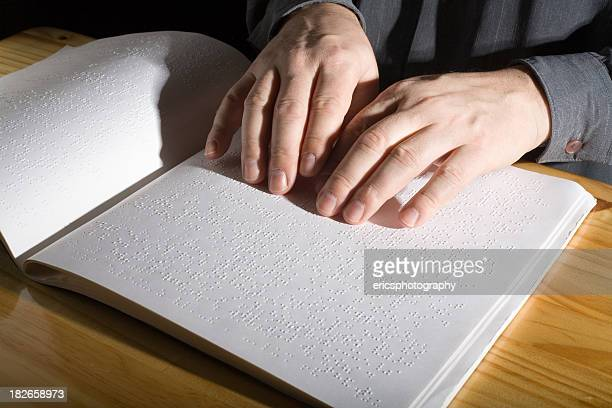 Man reading a Braille book