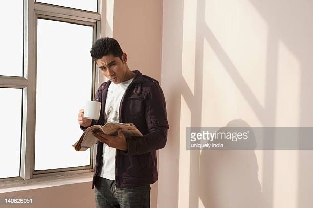 Man reading a newspaper and holding a cup of coffee