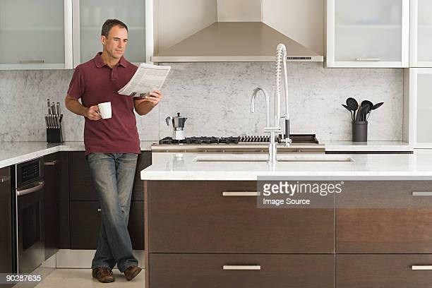 Man reading a newspaper in kitchen