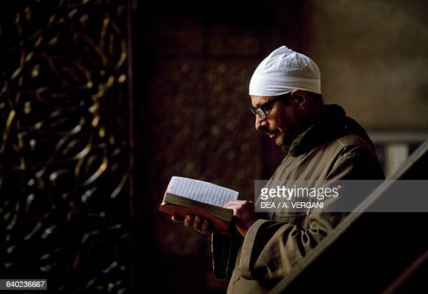 A man reading a sacred text in MosqueMadrassa of Sultan Hassan 14th century Cairo Egypt