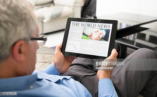 man reading  a World news newspaper on digital tablet
