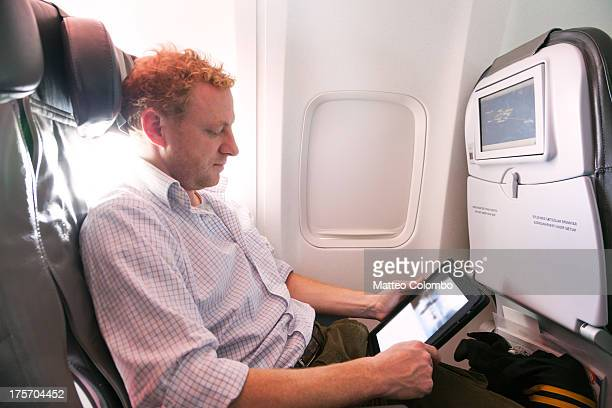 Man reading an ebook on his tablet on the plane