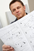 Man Reading Assembly Instructions For Flat Pack Furniture