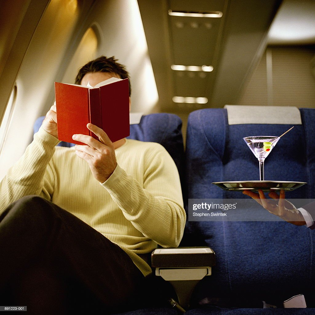 Man reading book, being served martini, in first class on airliner : Stock Photo