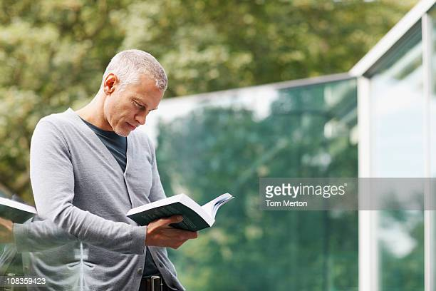 Man reading book on balcony