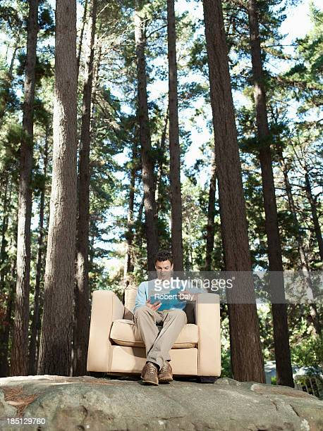 A man reading books outdoors in the woods
