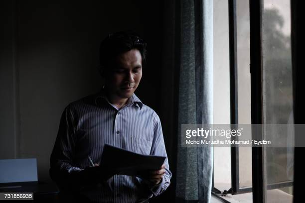 Man Reading Document While Standing By Window At Home