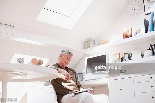 Homme lisant dans un bureau à domicile