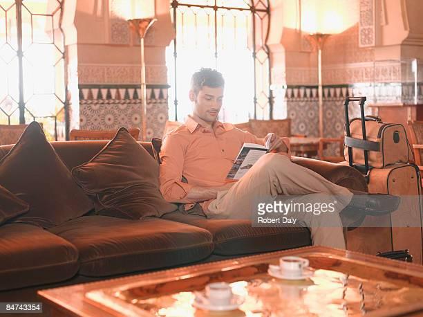 Uomo di lettura nella lobby dell'hotel