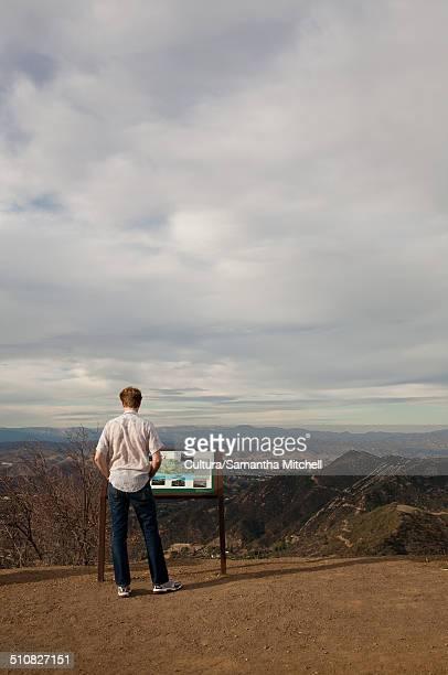Man reading information sign, California, USA
