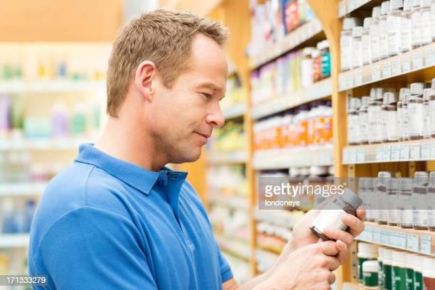 Mann liest Anweisungen Tablettenfläschchen