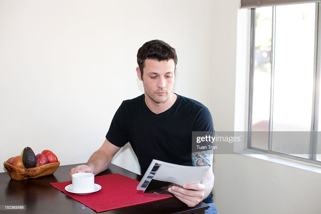 Man reading magazine at home : Stock Photo