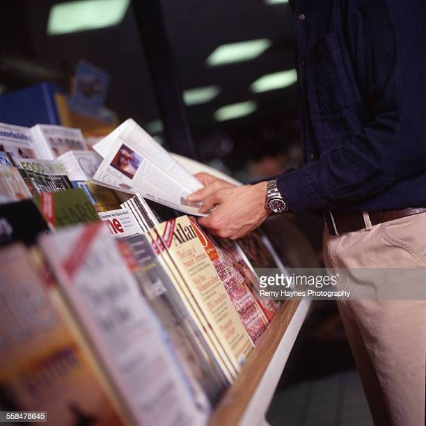 Man reading magazine at stand