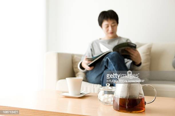Man reading magazine on sofa with tea on coffee table