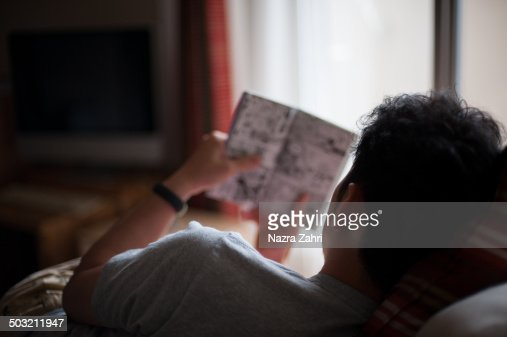 Man reading manga comic at home